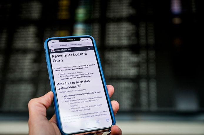 Het Passenger Locator Form op een smartphone op Brussels Airport, archiefbeeld.