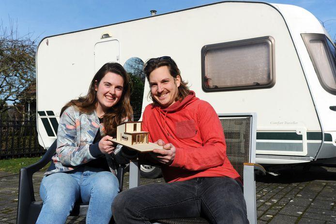 Niels Poppe en Janne Sophie van den Hamer voor hun caravan met de maquette van hun huisje.