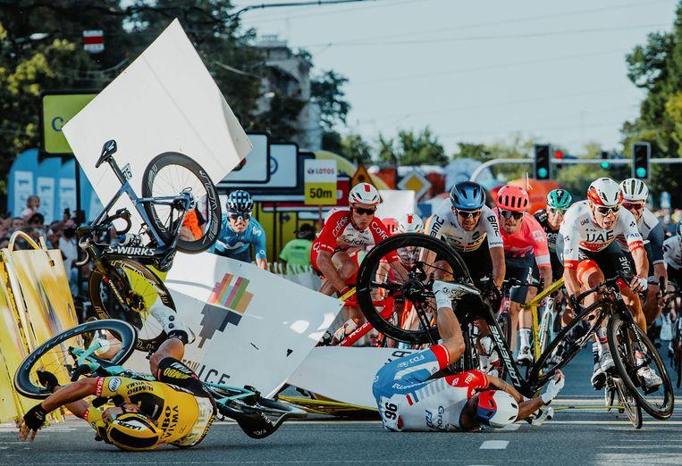 De crash in de Ronde van Polen, Fabio Jacobsen is hier al buiten beeld verdwenen, zijn fiets vliegt linksboven door de lucht. Groenewegen, in het geel vooraan, kwam zelf ook ten val.  Beeld AFP