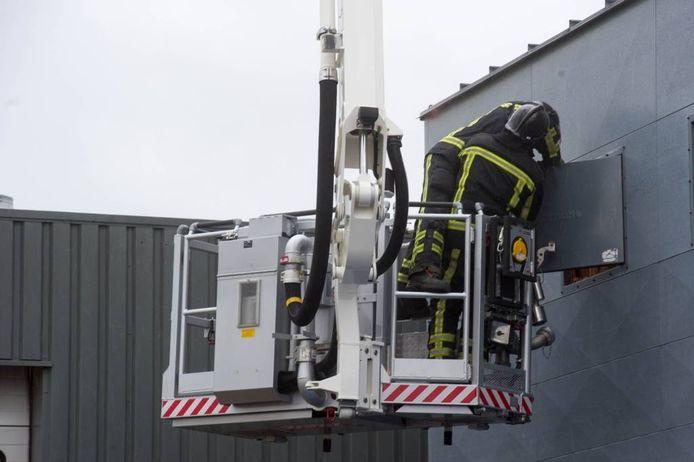 Met behulp van een hoogwerker bedwingen brandweerlieden het vuur in de afzuiginstallatie. Foto Bert Kamp