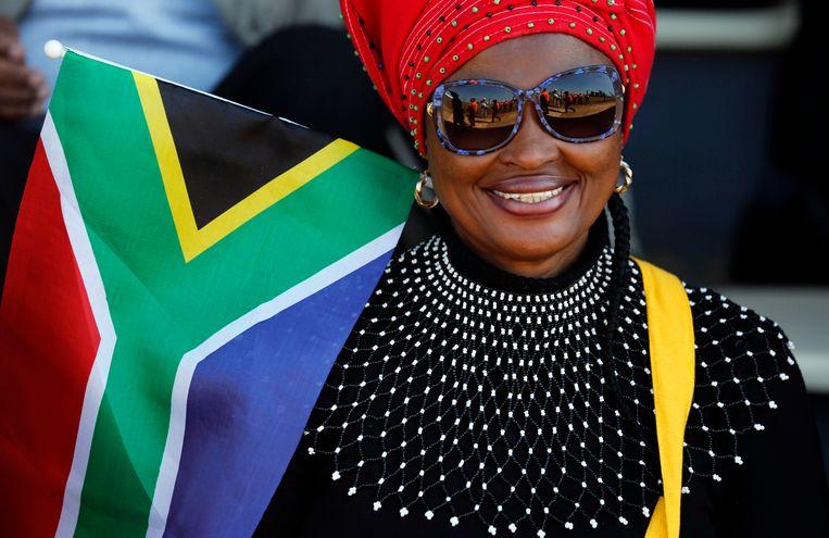 Een vrouw viert met Zuid-Afrikaanse vlag Freedom Day in Kwa-Thema, een township nabij Johannesburg.  Beeld AP