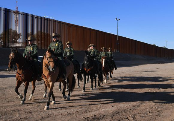 Leden van de  Amerikaanse Border Patrol-politiedienst  patrouilleren te paard aan de grens met Mexico in Calexico (Californië). Een veiligheidshek scheidt de twee landen.