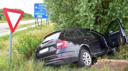Auto belandt in gracht en tegen boom na botsing op kruispunt