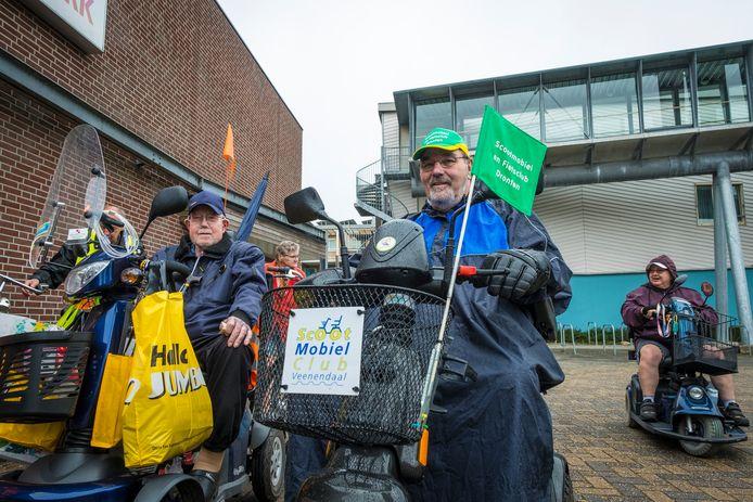 """Regen of niet, de scootmobielers waren blij met een uitje. ,,De gezelligheid, dat maakt het zo mooi"""", meent Bert Schoemaker (71, met groene pet)."""