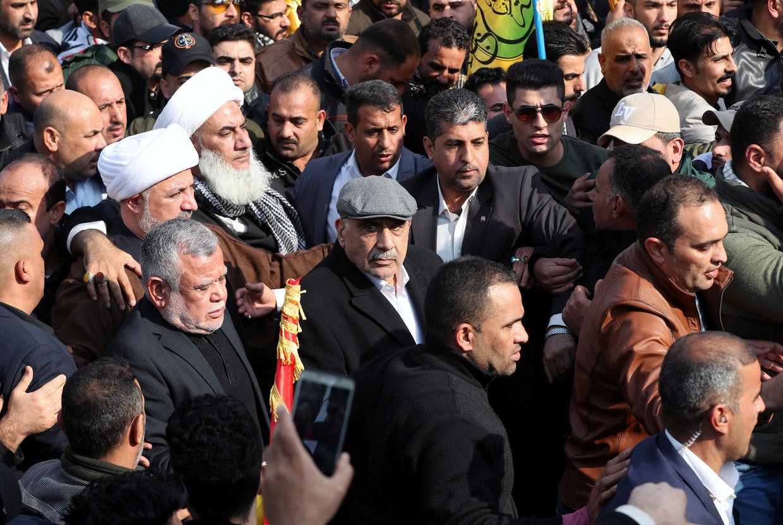 De Iraakse premier Adel Abdul Mahdi (midden met pet) loopt zaterdag in Bagdad mee in de rouwstoet van de Iraanse generaal Qassem Soleimani. Beeld REUTERS