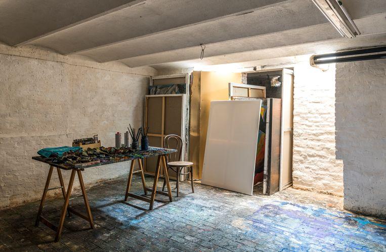 De donkere kelder, slechts verlicht door twee tl-lampen, is Hermans atelier.  'Daglicht haalt me uit mijn concentratie. Tijdens het schilderen wil ik geen besef van tijd.  Ik stop pas als ik klaar ben.' Beeld Luc Roymans