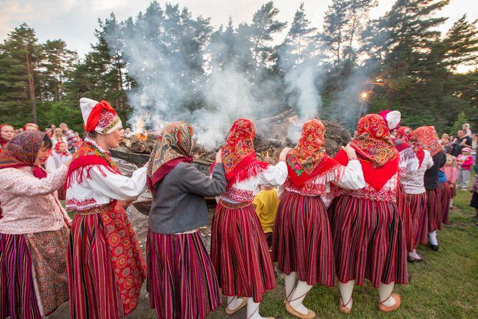 Vrouwen in traditionele kostuums die rituele dans en zang uitvoeren om de zomerzonnewende te vieren en om respect te betuigen aan een oude vissersboot die in brand staat.