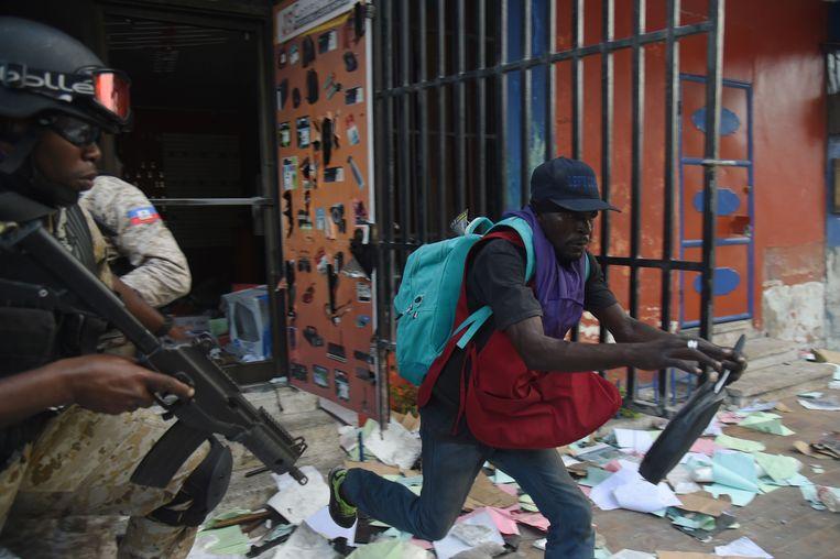 De Haïtiaanse politie probeert een man te arresteren die een winkel plunderde in de hoofdstad Port-au-Prince tijdens rellen tegen president Jovenel Moise. Beeld AFP