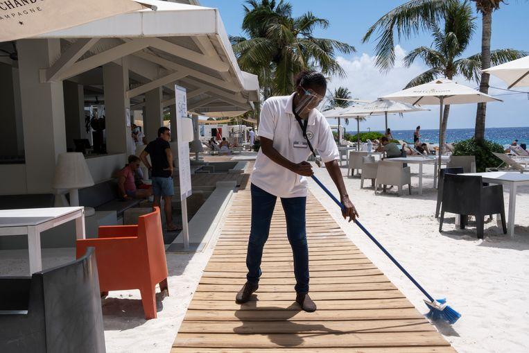 Een medewerker van een strandtent houdt de boel aan kant. Beeld Sabine van Wechem