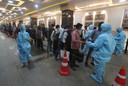 De temperatuur van treinreizigers in Mumbai wordt gemeten.