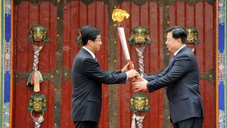 De inmiddels vervangen Zhang Qingli overhandigt het olympisch vuur aan Qin Yizhi, de communistische partijleider in Lhasa, in 2008. © afp Beeld