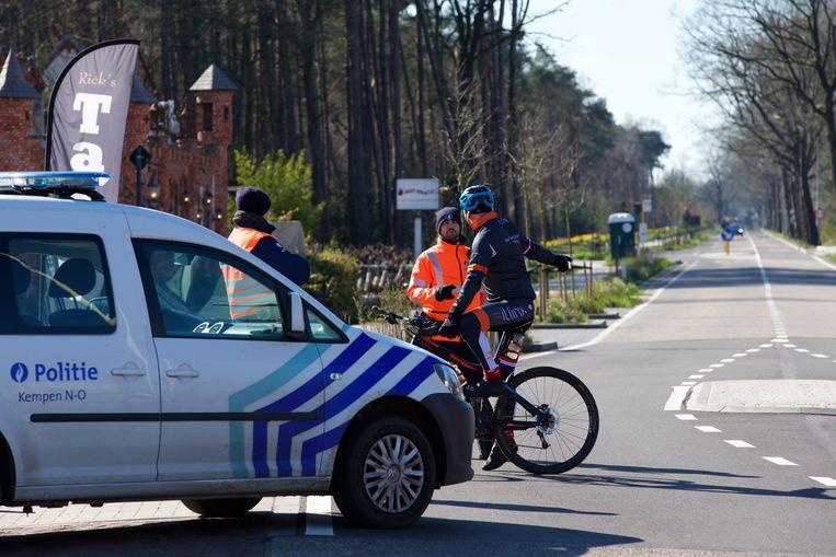 De politie ondervraagt een fietser aan de Belgisch-Nederlandse grens. Beeld Photo News