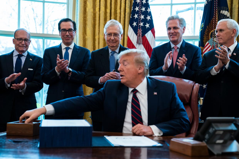 Donald Trump zoekt een pen om een pakket noodmaatregelen te ondertekenen. De president was donderdag nog niet echt overtuigd van de ernst van de zaak, vrijdag opeens wel. Beeld AP