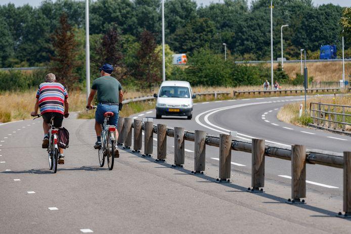 Een houten vangrail tussen Oud Gastel en de A17 scheidt het fietsverkeer van de autoweg N641.