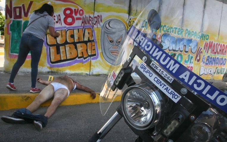 Een forensisch onderzoeker neemt een foto van een dood geschoten man in Acapulco. Beeld ap