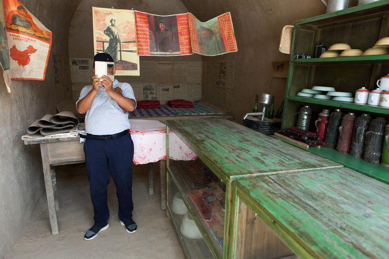 Liangjiahe. Een toerist bezoekt een winkel in het dorp waar Xi Jinping tijdens de Culturele Revolutie verbleef. Beeld Foto Wassink Lundgren