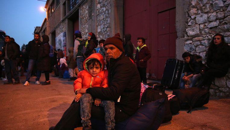 Vluchtelingen wachten in de Griekse havenstad Piraeus op vervoer naar een opvangkamp bij Athene. Ze zijn per schip opgehaald van het eiland Lesbos, waar de meeste bootvluchtelingen arriveren. Beeld null