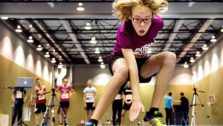 Papendal, zondag: een tiener test haar wendbaarheid door voorwerpen aan te tikken die voor en opzij van haar op de grond liggen. Beeld Klaas-Jan van der Weij /  De Volkskrant