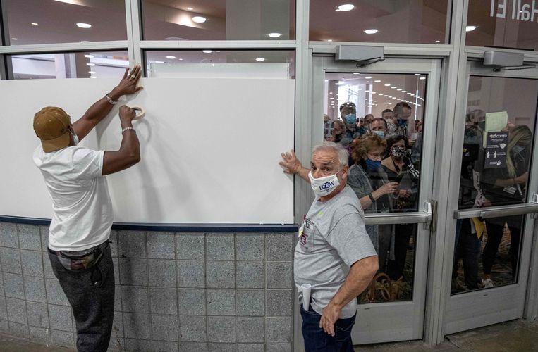 Verkiezingsmedewerkers plakken de ramen van het stembureau in Detroit af, zodat Trump-aanhangers niet meer naar binnen kunnen kijken.  Beeld AFP