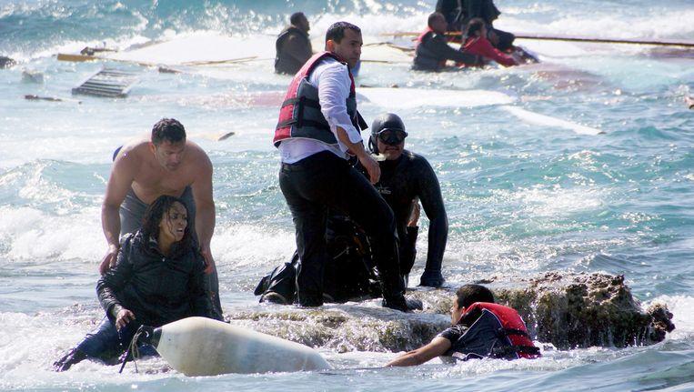 Bij het Griekse eiland Rhodos worden drenkelingen van een gezonken vluchtelingenboot aan wal geholpen. Beeld ap