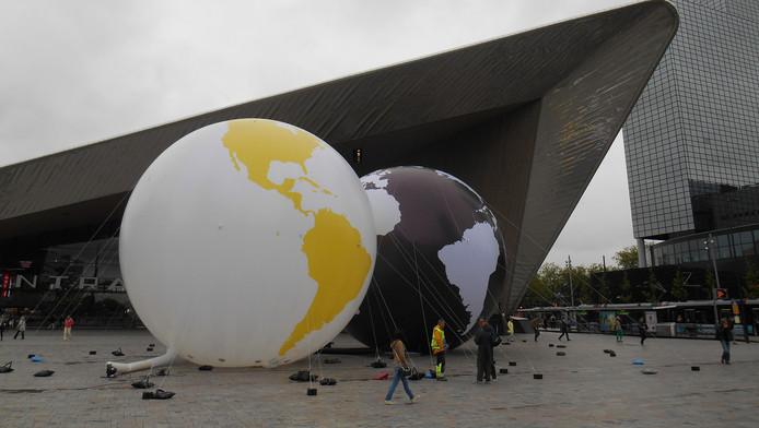 Kunstenaar Olafur Eliasson bekijkt hoe de gele ballen bij Rotterdam Centraal staan.