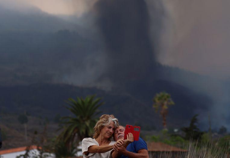 Een stel neemt een selfie voor de uitbarstende vulkaan in het dorp Los Llanos de Aridane. Beeld Reuters