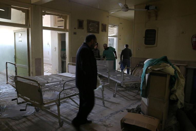 Mensen nemen de schade op in gebombardeerd ziekenhuis Omar Bin Abdulaziz. Beeld reuters