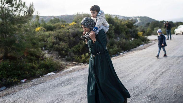 Een vluchteling loopt terug naar het Griekse Idomeini na een mislukte poging de grens naar Macedonië over te steken. Beeld reuters