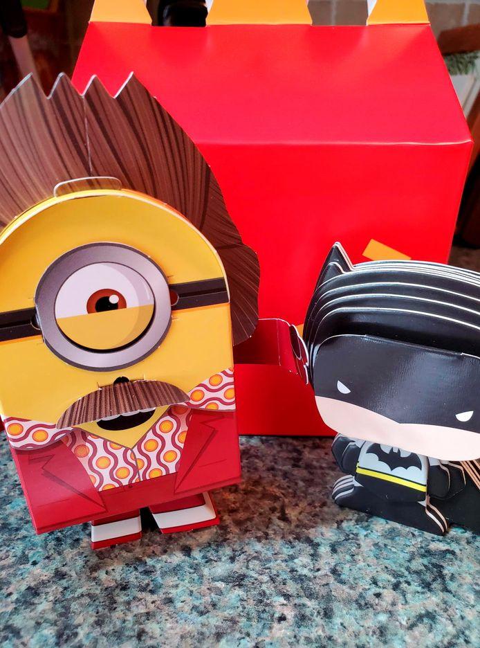 Een voorbeeld van de nieuwe Happy Meal-speeltjes. Kinderen zouden kartonnen Batman- en Minion-poppetjes zelf in elkaar kunnen knutselen.