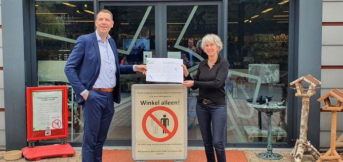 Wethouder Horsthuis-Tangelder overhandigt een voucher aan eigenares Henrika Quik van dierenshop Het Molentje in Elst.