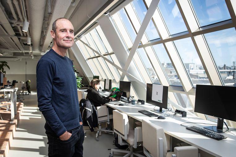 Pieter van der Does op zijn favoriete plek in het nieuwe kantoor van Adyen op het Rokin, de bovenste verdieping van het  gebouw met vensters die uitkijken op de daken van de Wallen. Beeld Dingena Mol