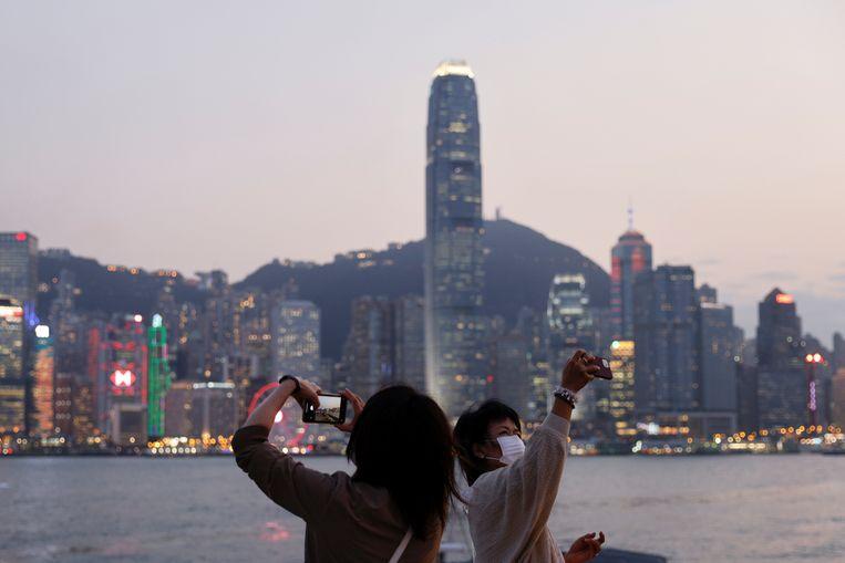 Toeristen fotograferen zichzelf voor de skyline van Hongkong. Beeld Reuters