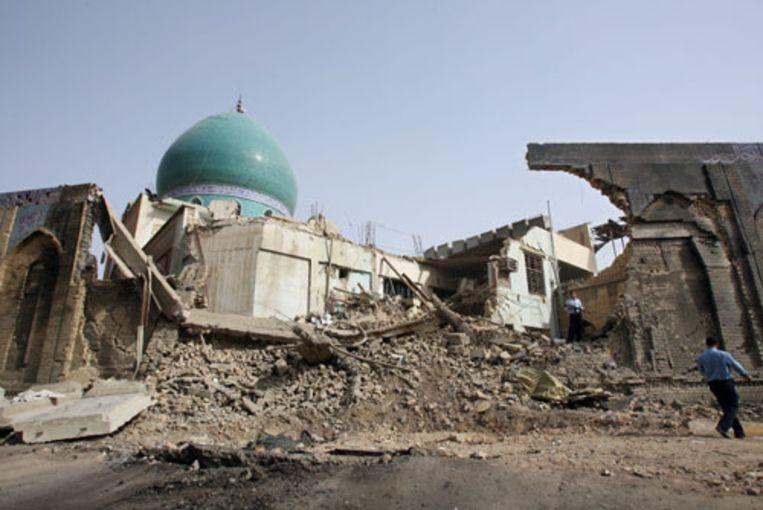 Iraakse politiemannen bewaken woensdag in de Iraakse hoofdstad Bagdad de moskee die dinsdag door een aanslag zwaar beschadigd is. De aanslag heeft zeker 75 mensen het leven gekost en er raakten zeker 130 mensen gewond. (AFP) Beeld
