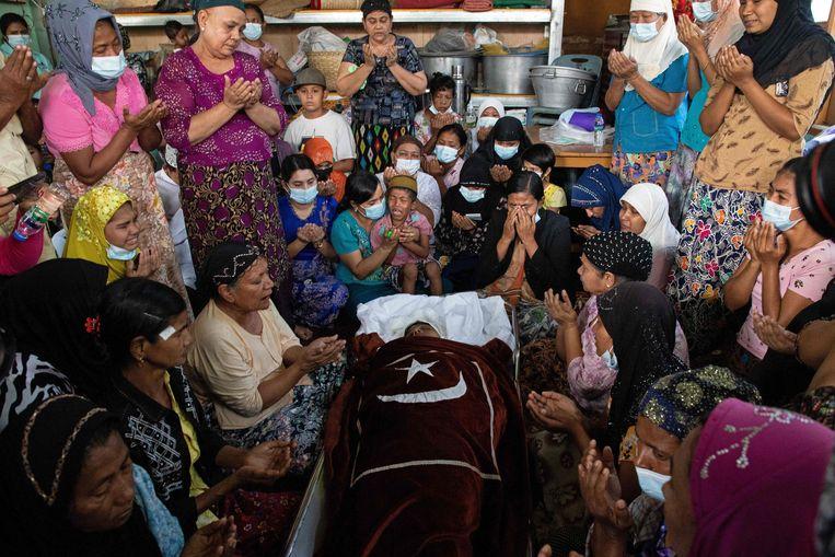 Familieleden rouwen en bidden naast het lichaam van een vrouw die om het leven is gekomen tijdens een demonstratie tegen de militaire coup in Myanmar. Beeld AFP