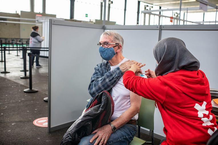 Een zeventiger krijgt een prik met het Pfizer-vaccin in de GGD-vaccinatiestraat in de RAI in Amsterdam. Beeld Guus Dubbelman / de Volkskrant