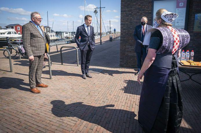 Minister De Jonge wordt samen met burgemeester Van de Groep van Bunschoten ontvangen door een Spakenburgse in de traditionele klederdracht. Voor het gezelschap staat de lekkernij Spakenburgs hart al klaar.