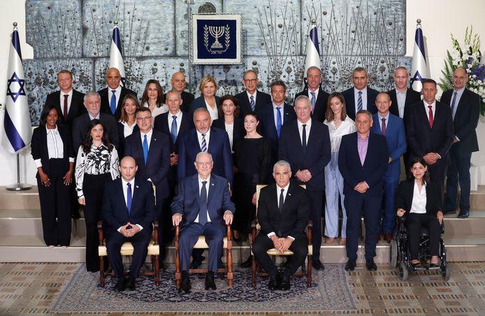 Premier rang : Le nouveau Premier ministre israélien Naftali Bennett (G), le président israélien Reuven Rivlin (C) et le Premier ministre suppléant et ministre des Affaires étrangères Yair Lapid (D) posent pendant une photo commune avec les nouveaux ministres du gouvernement à la résidence du président à Jérusalem, Israël, le 14 juin 2021.