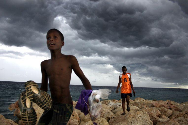 Twee jongens zijn gaan vissen aan de kust van Curaçao. Op het eiland bepaalt de zee het ritme van het leven.  Beeld Bart Mühl
