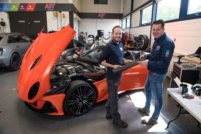 De magisch oranje gekleurde bolide wordt bij AST door monteur Robbin van der Sluis (links) voorzien van een alarmsysteem. Rechts Tom Arendsen van AST Vriezenveen.