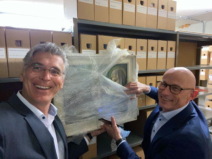 Wethouders Willy Brink (l) en Gérard de Wildt - niet op 1,5 meter maar beiden zojuist negatief getest op corona - tonen het ontdekte schilderij 'Sainte Bernadette'.
