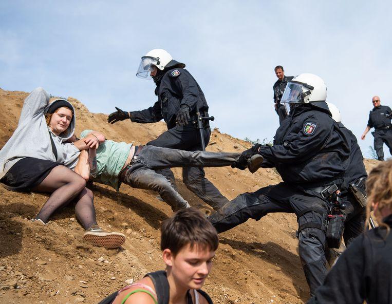 Agenten proberen demonstranten te verhinderen het bos te betreden uit protest tegen de houtkap. Beeld AFP