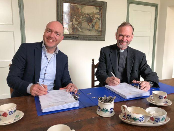 Pastoor Roland Kerssemakers (rechts) tekent het aannemingscontract met Richard Ceelen van bouwbedrijf Berghege.