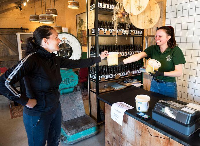 Verkoopster Femke van de 'Boer Bert Shop' verkoopt een emmertje biest aan een klant.