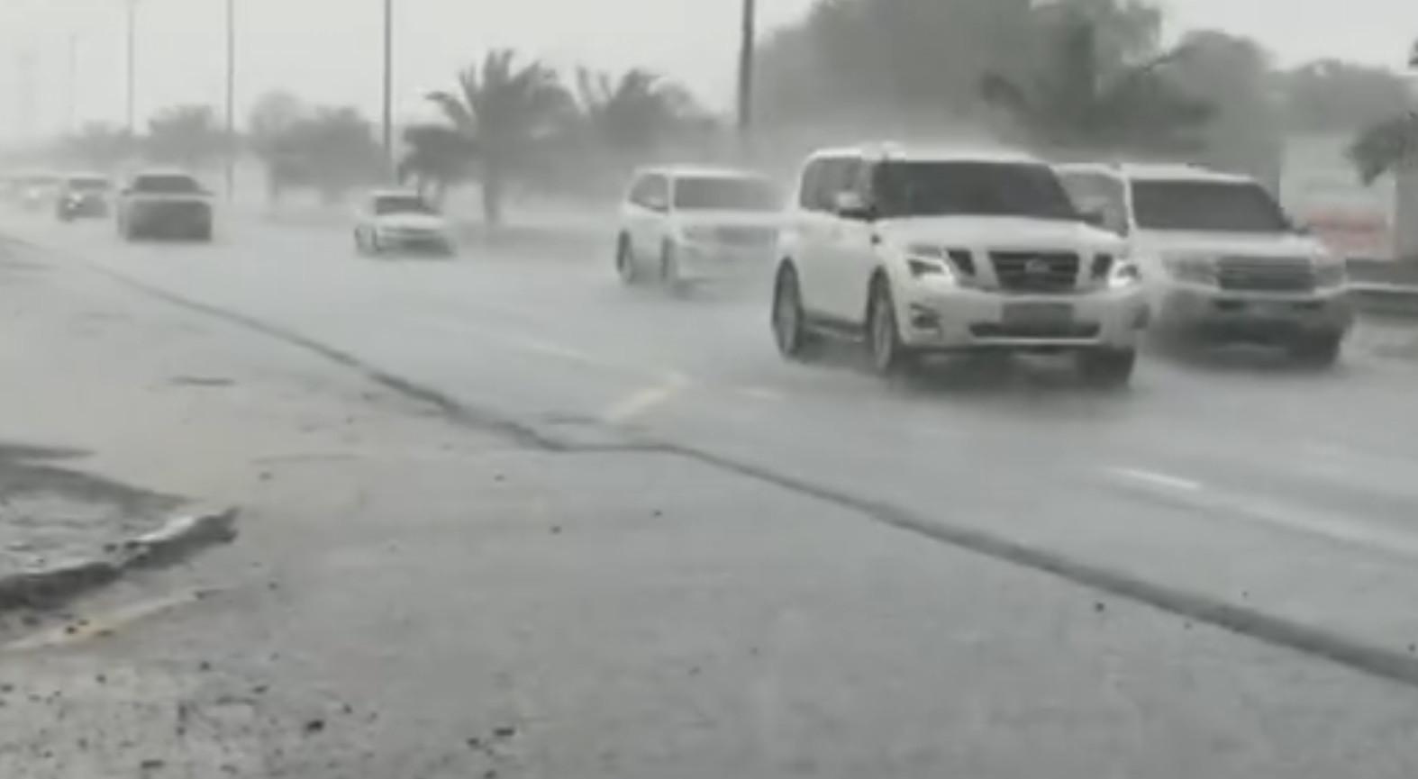Auto's trotseren de hevige regenbuien in het emiraat Duabi.