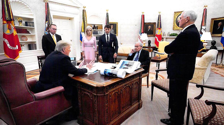 President Trump spreekt in de Oval Office met journalist Bob Woodward, die tegenover hem zit. Ook vicepresident Mike Pence is aanwezig, evenals een aantal stafmedewerkers.  De foto is gemaakt in december 2019. Beeld White House