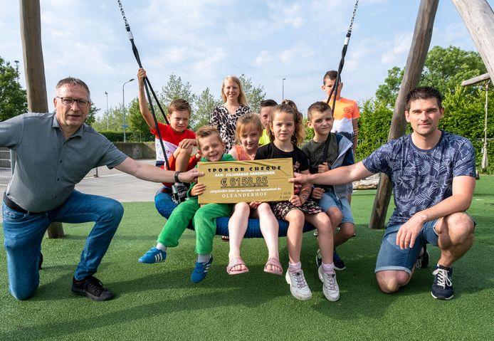Wim Dodmond (links) en Patrick Siereveld van Stichting Behoud Julianabad krijgen een cheque van 6158,85 euro van de leerlingen van de Oleanderhof in Arnemuiden. Het geld is bedoeld voor een speeltoestel bij het zwembad.