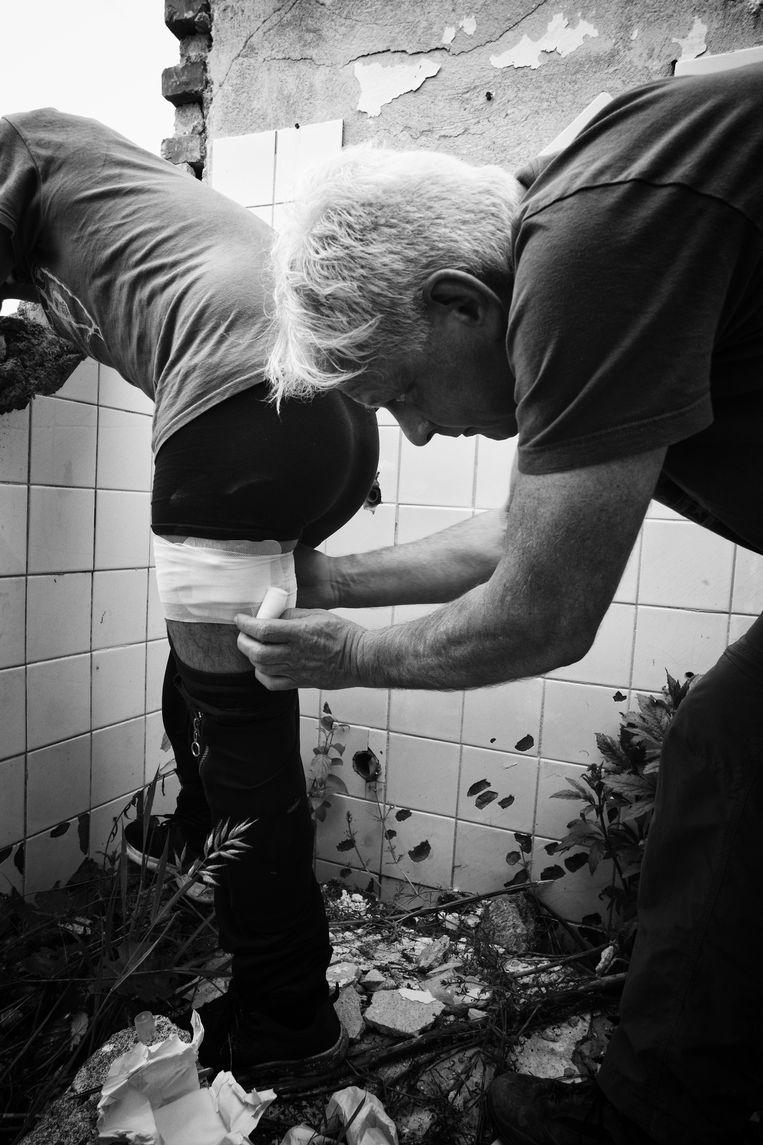 Arts Peter Scholten helpt een vluchteling in Velika Kladusa, Bosnië. Beeld Eddy van Wessel