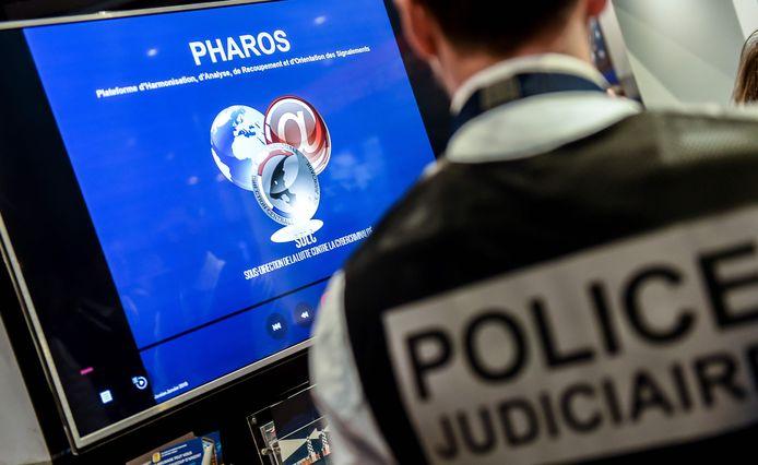 Een lid van de Franse gerechtelijke politie bekijkt de website van platform Pharos dat er alles aan deed om de foto van het afgehakte hoofd van Twitter en Facebook te laten verwijderen.