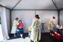Een zorgmedewerker wordt in de tent getest.