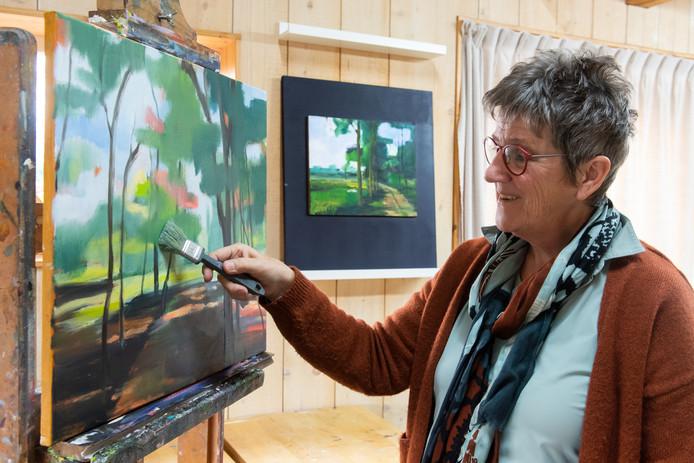 Kunstenaresse Joke Oomen heeft een prijs gewonnen met een schilderij. Ondertussen is ze alweer aan iets nieuws bezig. Het winnende werk is te zien op de achtergrond.
